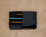 Black leather foldover clutch bag featuring Baule cloth; handmade in Africa by Chameleon Goods