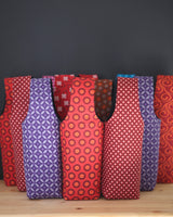 Wine (n.) - A hug in a glass. Give your friend *and* your wine a hug when you carry your bottle in one of our colorful wine totes.  Lightly padded, and fully lined, the wine carrier are handmade in Africa by Chameleon Goods.