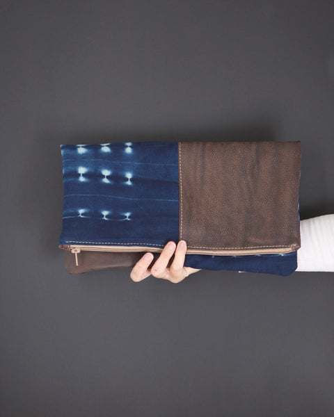Brown leather foldover clutch bag with indigo mud cloth; handmade in Africa by Chameleon Goods