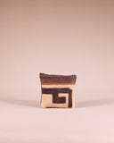 Front view of our mini brown leather zipper pouch with Kuba cloth. Handcrafted in Africa by Chameleon Goods.