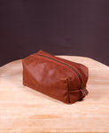 Medium-size hand stitched brown leather toiletry bag with zipper closure