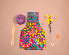 Small knitting bag for makers with a colorful waxed cotton print exterior. Handmade in Africa by Chameleon Goods.