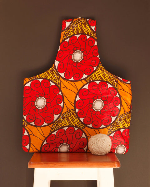 Large knitting bag for makers in a colorful red waxed cotton print. Handmade in Africa by Chameleon Goods.