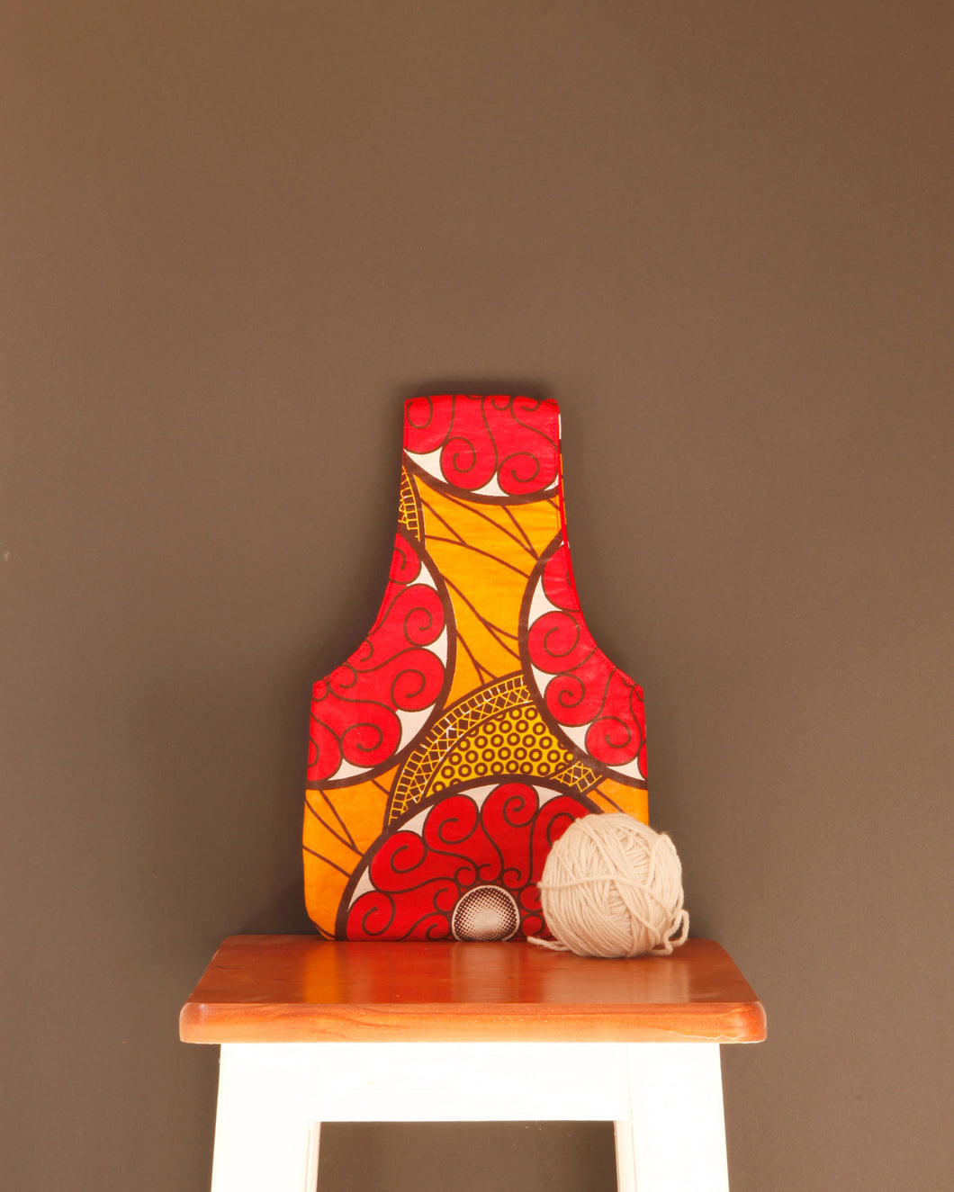 Small knitting bag for makers with a colorful, red waxed cotton print exterior.  Handmade in Africa by Chameleon Goods.