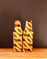 Wine (n.) - A hug in a glass. Give your friend *and* your wine a hug when you carry your bottle in this pretty waxed cotton print wine tote from Chameleon Goods.  Lightly padded, and fully lined, this wine carrier is handmade in Africa.