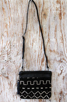 Front view of our black leather convertible clutch with crossbody strap and mud cloth. Handmade in Africa by Chameleon Goods.