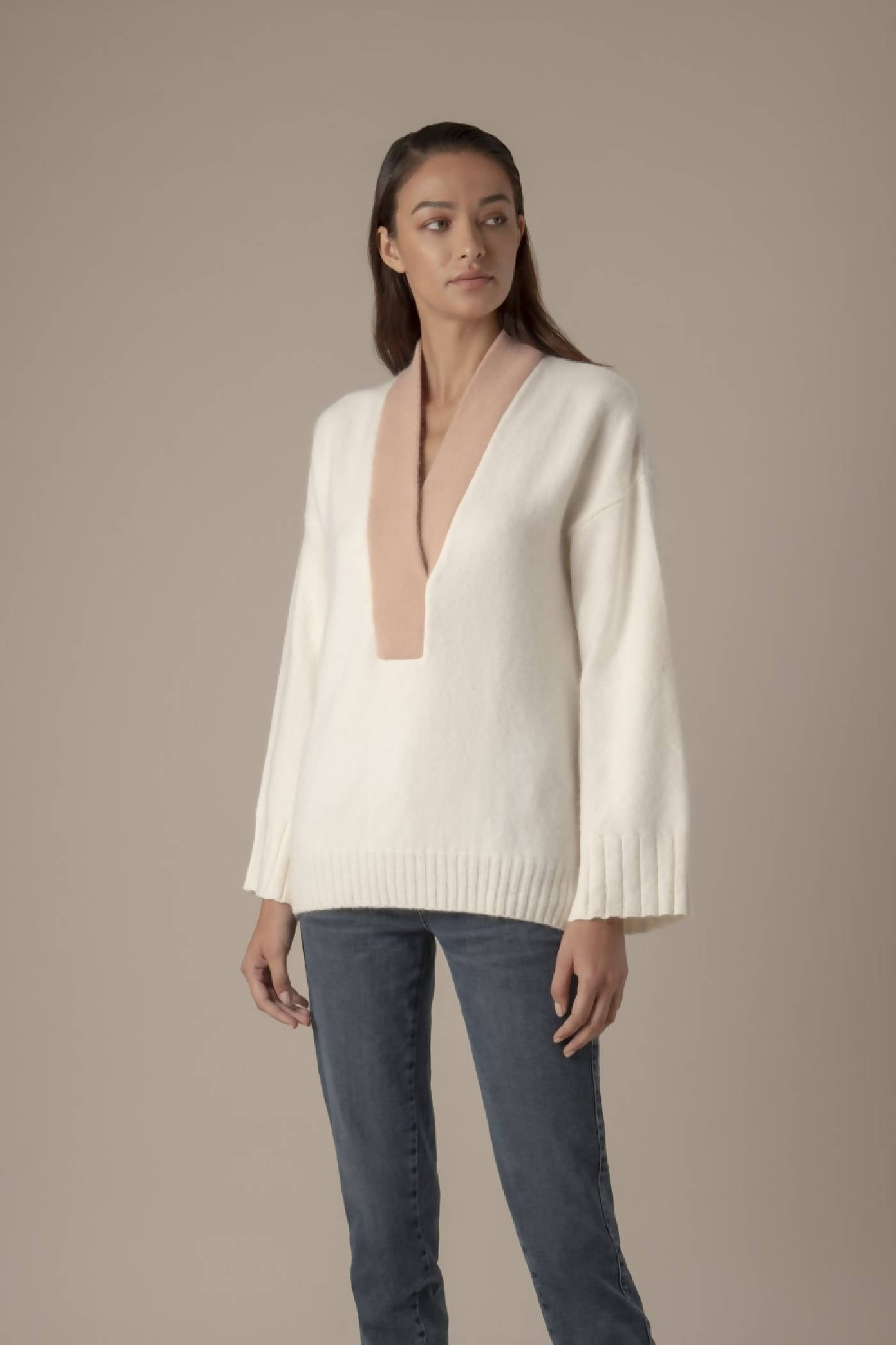 Soft and warm jumper in white with a statement deep V-neck in rusty rose and bell-bottom sleeves