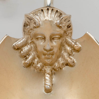 Close up of the mask on the Gorham Antique Coin Silver Figural Serving Scoop, Providence, RI, c. 1867