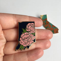 A hand holding an enamel pin shaped like the state of Indiana, featuring pin Pink peonies within the state outline.