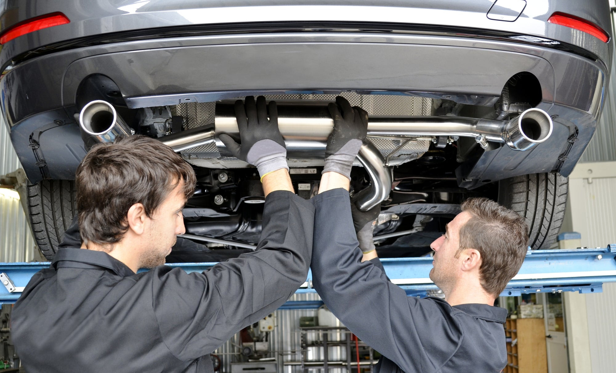 car mechanics installing exhaust system