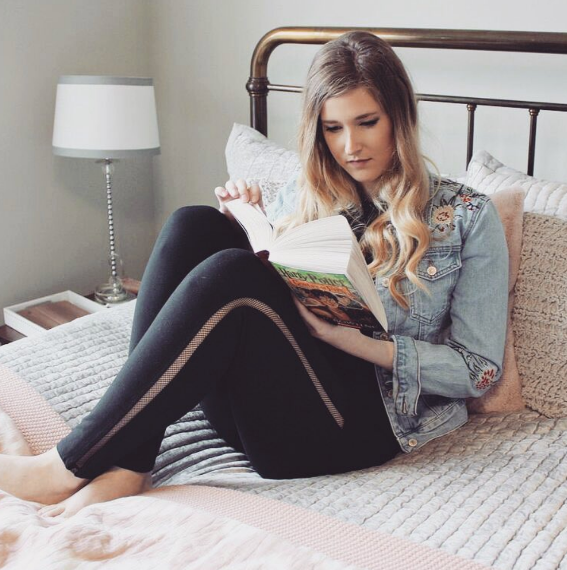 Girl wearing black mesh legging reading a book.