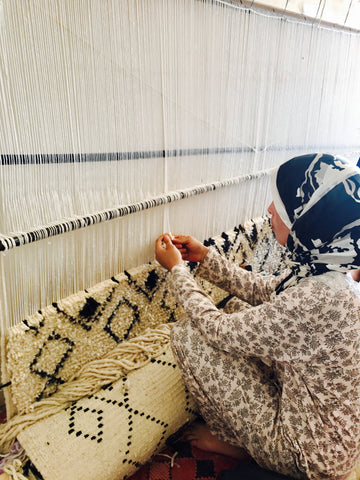 Moroccan woman hand weaving an Ait Bouguemez rug