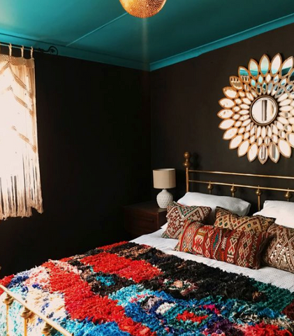 Dark painted bedroom with Moroccan cushions