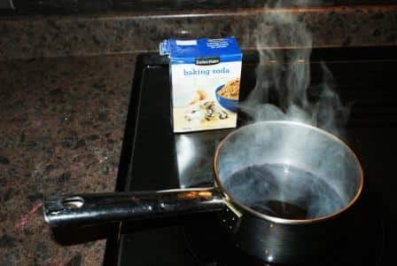 A pot with steam coming off of it and a box of baking soda behind it