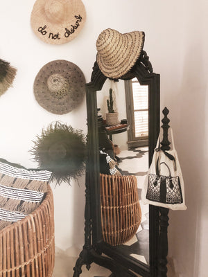 A mirror in a bedroom with beach hats and a vintage handbag bag hanging off of the side.