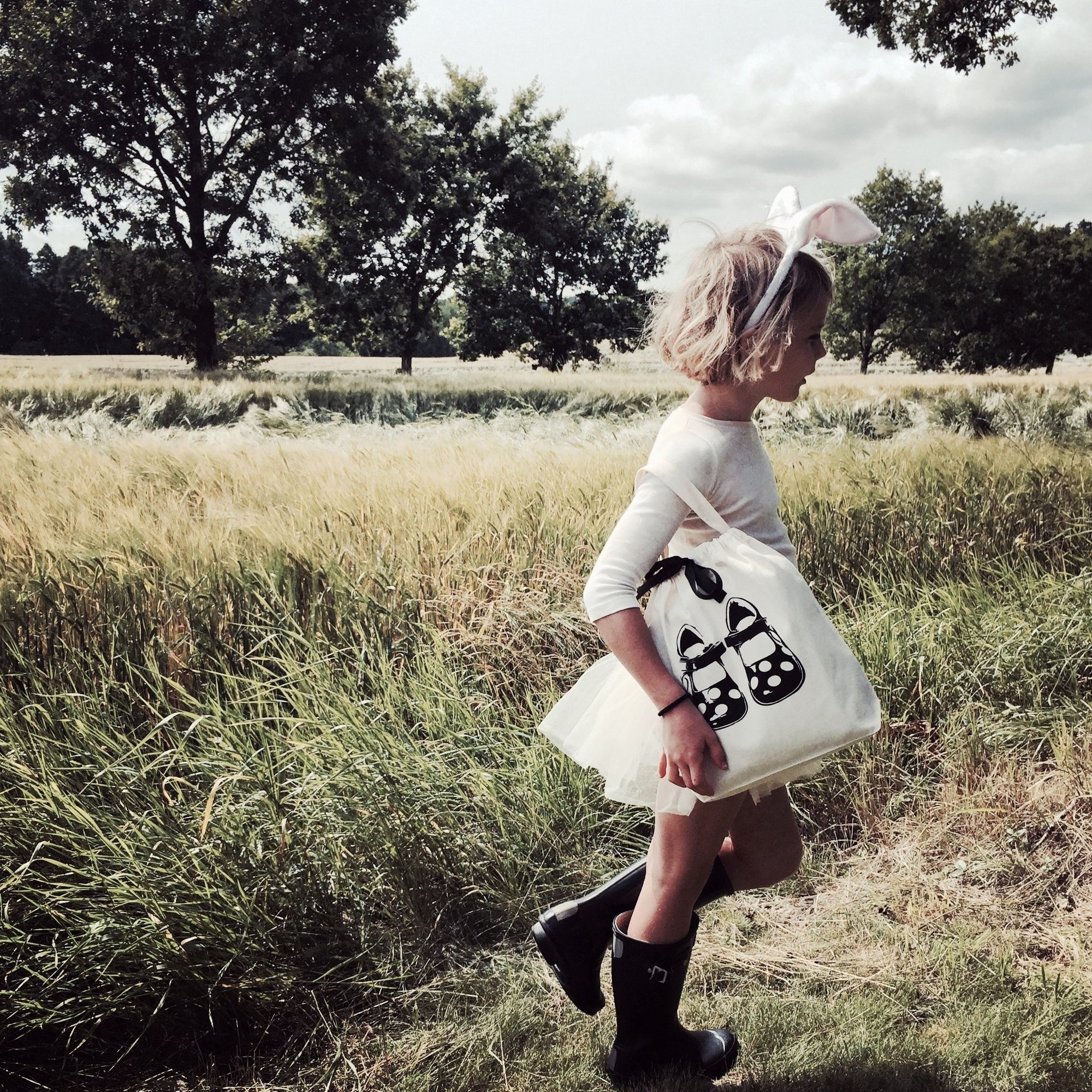 A child in a grassy field with a shoe bag.