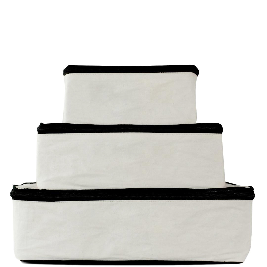 3 white packing cubes in large, medium and small.