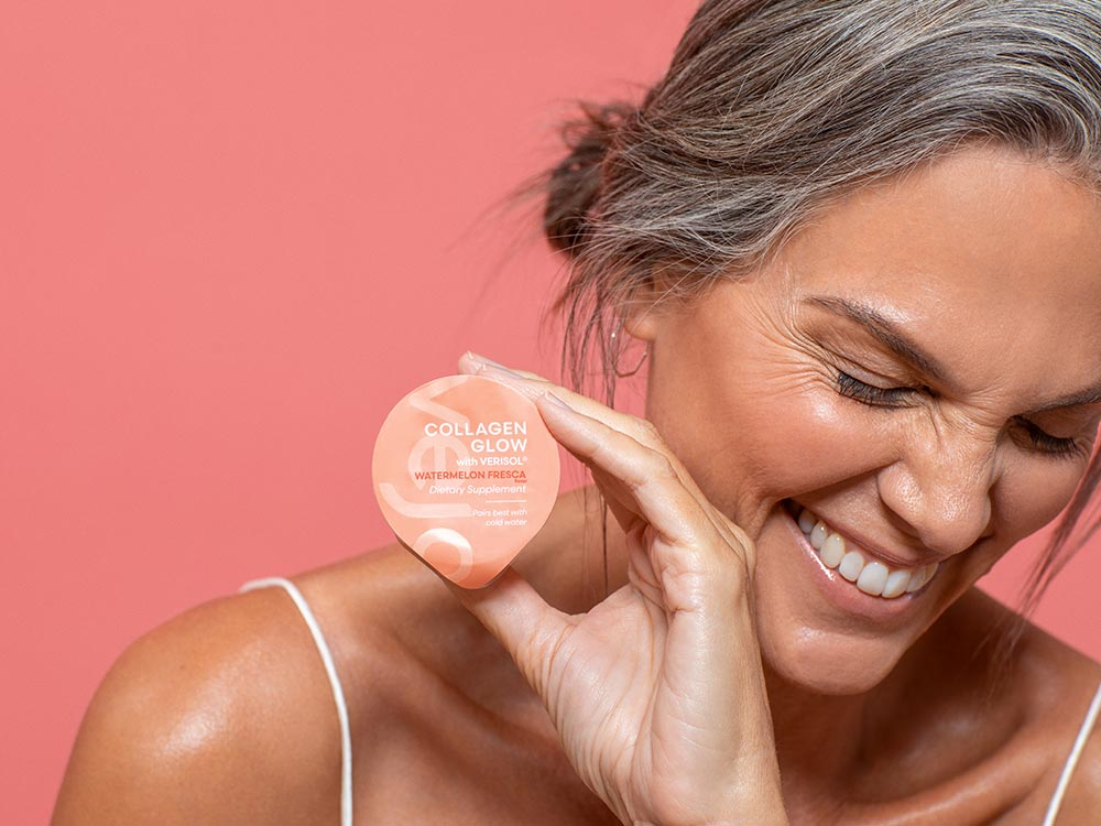 A close up of Vejo's Collagen Glow blend held by a woman laughing in front of a pink background.