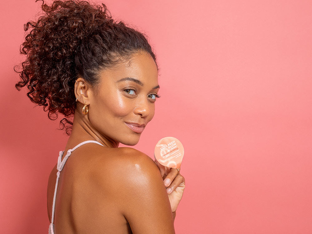 A close up of a woman holding Vejo's Collagen Glow pod standing in front of a pink backdrop.