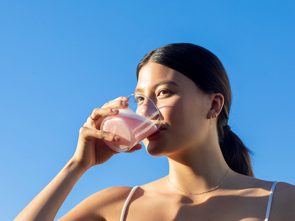 A woman drinking Vejo's Collagen Glow with the sun hitting her skin and glowing with a comforting blue sky background behind her.