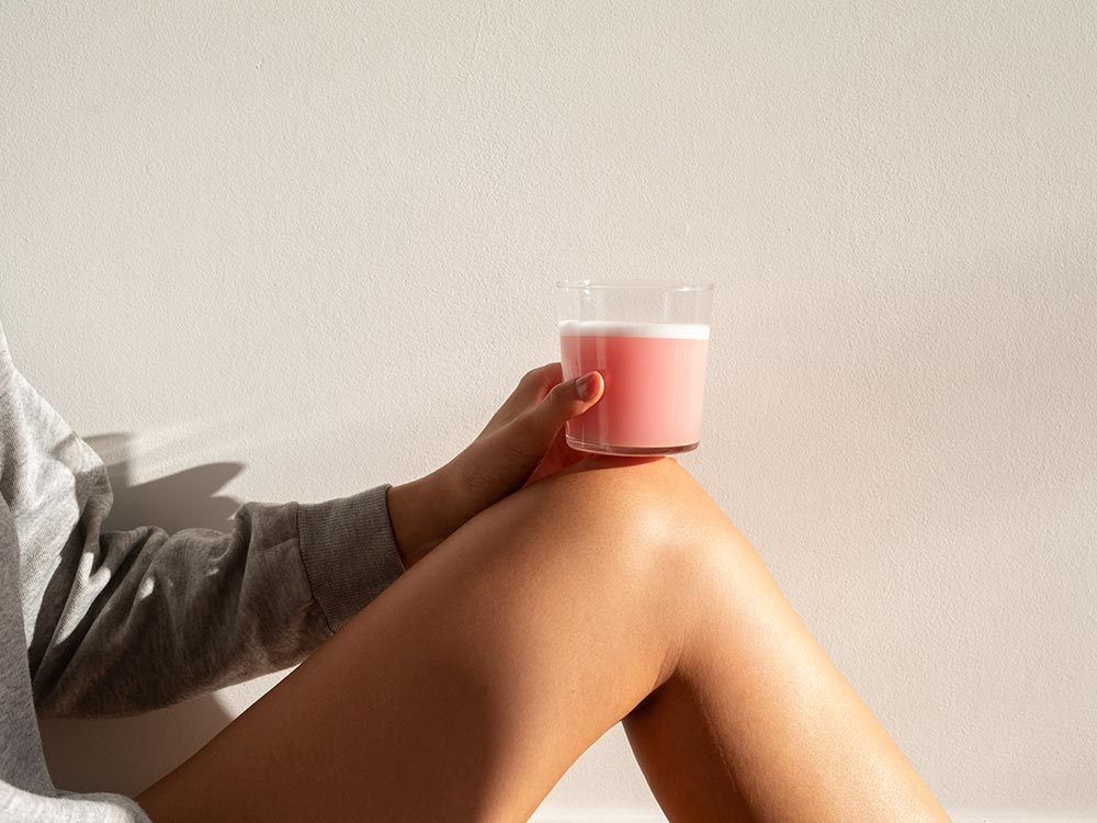 The morning sun hitting a blended smoothie of Vejo's Collagen Glow, resting comfortably on top of a woman's leg.