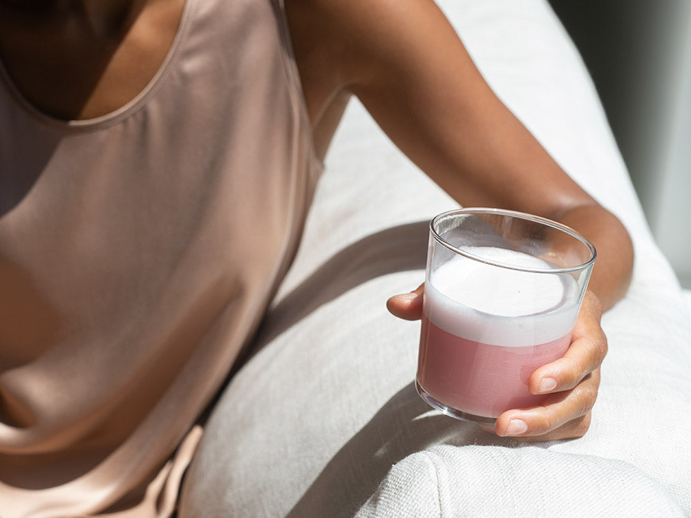A clear glass with Vejo's Collagen Glow pink smoothie sitting in it glistening from the shine of the sun on the edge of a white sofa.