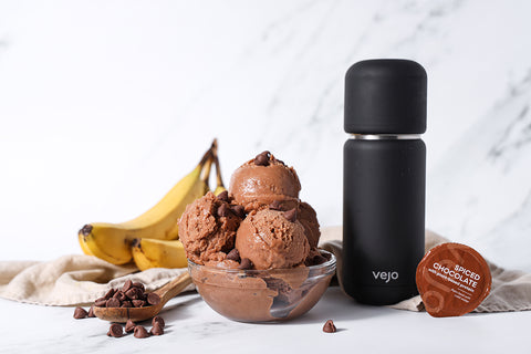 A bowl of chocolate nice cream beside a brown spiced chocolate Vejo blend and black Vejo blender.