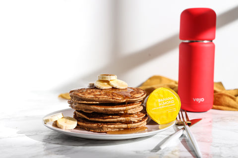 A stack of savory banana pancakes beside a yellow banana almond Vejo blend and red Vejo blender.