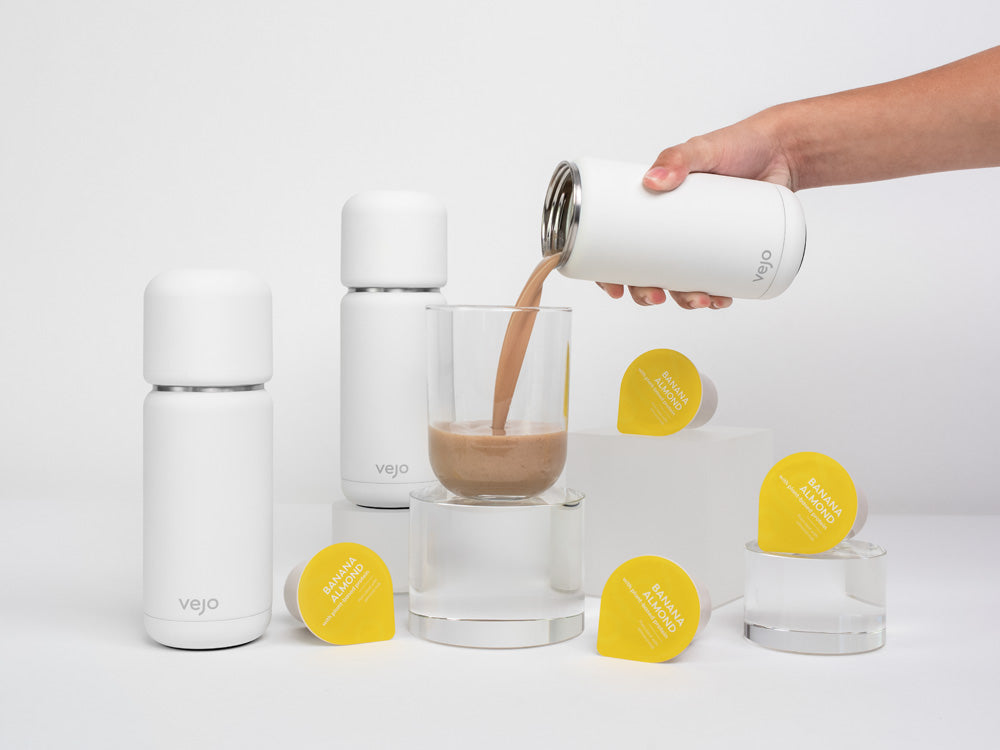 Vejo's Banana Almond blend being poured into a clear glass by a white Vejo blender, surrounded by 2 other white Vejo blenders & Banana almond blends.