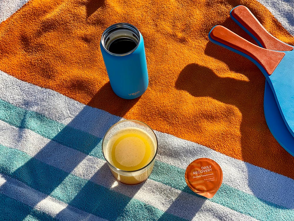 A blue vejo blender sitting on a orange and blue striped beach towel by a glass of daily recovery blend and ping pong paddles.