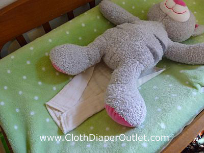 Lay your baby on top of the unfolded cloth diaper end