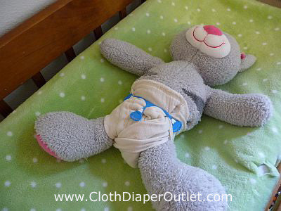 Pull the diaper wings from behind baby up to the tummy panel