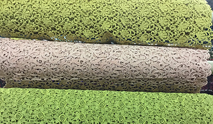 Green and grey rolls of lace fabric at the Lens Designer Fabric Store in North York