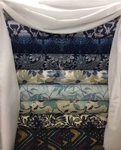 Blue and cream floral upholstery fabrics, stacked, framed by white drapery