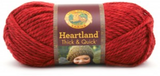 A ball of Lion Brand Heartland Thick & Quick in colourway Redwood (heathered bright red)