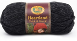 A ball of Lion Brand Heartland Thick & Quick in colourway Black Canyon (heathered black)