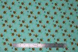 Flat swatch teal bee fabric (pale teal/aqua fabric with cartoon yellow and black bees tossed allover)