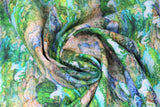 Swirled swatch creek fabric (small repeated creek scene allover - green trees, green moss surrounding flowing blue river, brown and grey rocks, tiny light blue unicorn/horse silhouettes throughout)