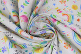 "Swirled swatch sweet dreams fabric (white fabric with small tossed colourful emblems allover: rainbows, hearts, flowers, ""Sweet dreams"" text, ""Learn and grow"" text, etc.)"