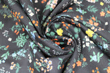 Swirled swatch Strawberry Fields collection floral printed fabric in pressed floral (small multi-coloured floral bunches on black)