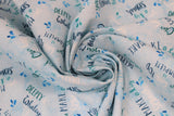 Swirled swatch whale themed fabric in Big Splash Light (splash and whale themed text collage on light blue)