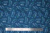 Flat swatch whale themed fabric in Big Splash Dark (splash and whale themed text collage on dark blue)