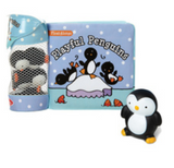 Playful Penguins book made of pillowed vinyl pages with a mesh tube attached to the spine. The tube contains black and white toy penguins and the book cover shows three penguins playing on an ice floe in the middle of water with a night sky behind them.