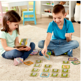 Two children on carpet in kids room playing with book and puzzle