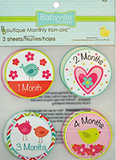 "Package of 3 sheets of iron-ons, with ""1 month"" (turquoise bird with pink and orange flowers), ""2 months"" (pink nested hearts with turquoise flower), ""3 Months"" (pink bird and orange bird), and ""4 Months"" (yellow bird on pink flowers) circular badges"