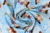 Swirled swatch magical themed printed fabric in print fairies (light blue marbled fabric with tiny blue stars and cartoon brunette fairies with two side buns and gold star wands, pink/blue/green/purple dresses)