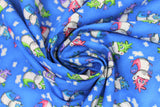 Swirled swatch magical themed printed fabric in print dragons (medium blue fabric with tiny white cloud puffs and cartoon dragons in green/pink/blue/purple colours)
