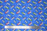 Flat swatch magical themed printed fabric in print dragons (medium blue fabric with tiny white cloud puffs and cartoon dragons in green/pink/blue/purple colours)