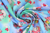 Swirled swatch magical themed printed fabric in print unicorns (sky blue and light green marbled fabric with white cartoon unicorns with pink manes/tails standing on mini cloud platforms with 1/4 rainbows, tossed white and pink hearts)