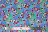 Flat swatch magical themed printed fabric in print unicorns (sky blue and light green marbled fabric with white cartoon unicorns with pink manes/tails standing on mini cloud platforms with 1/4 rainbows, tossed white and pink hearts)
